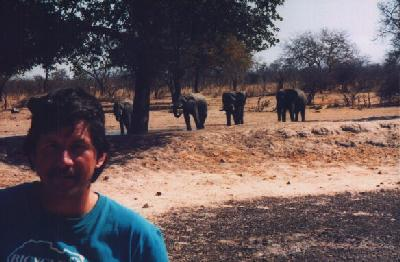 Ted with a heard of elephants in the background.